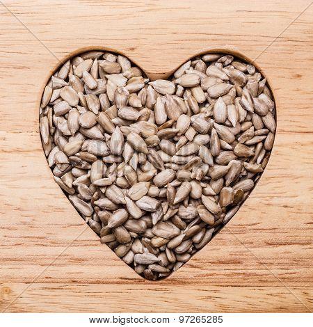Heart Shaped Sunflower Seeds On Wood Surface