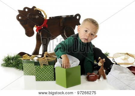 An adorable preschooler dressed up for Christmas, surrounded by gifts.  He's looking up as he digs into one box.  On a white background.