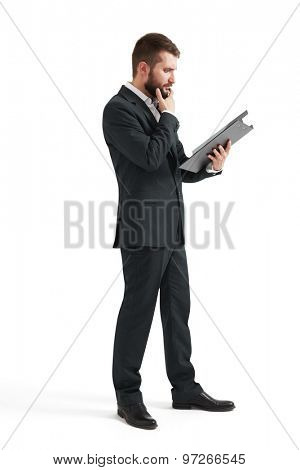 full length portrait of serious businessman in formal wear reading documents in black folder. isolated on white background