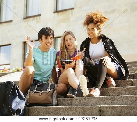 cute group of teenages at the building  university with books huggings, back to school