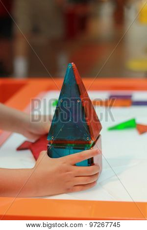 Child building a house with magnetic blocks