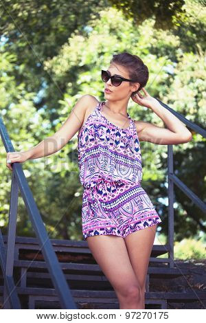 beautiful young woman in summer short jumpsuit and sunglasses outdoor shot
