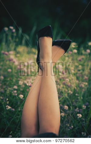 female legs in high heel shoes in grass