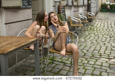 Two girls whispering sitting on the street.