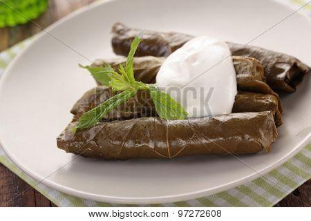 Sarma with mint leaves and yogurt on a plate