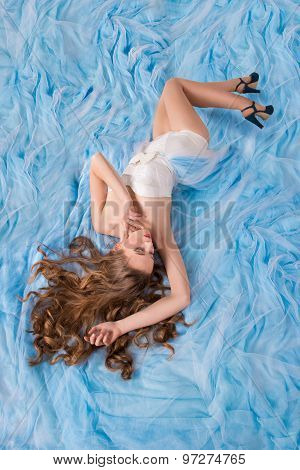 Beautiful Girl Lies On Plume Of Her Long Dress