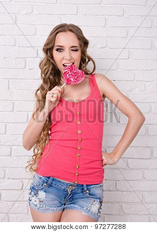 Beautiful Girl Licking A Pink Lollipop. Girl Has A Very Long Hair
