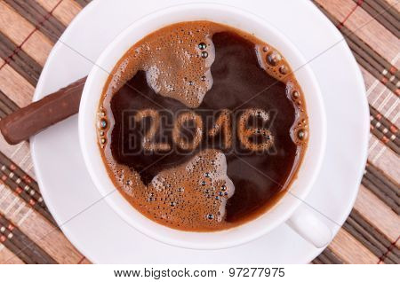 Cup of coffee with New year numbers 2016 on the coffee surface