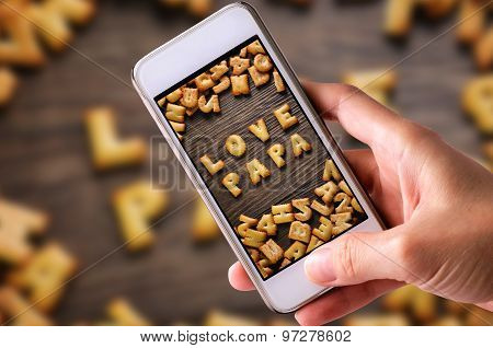 using mobile phones to take photos of Cookies ABC in the form of word LOVE PAPA alphabet on old wood
