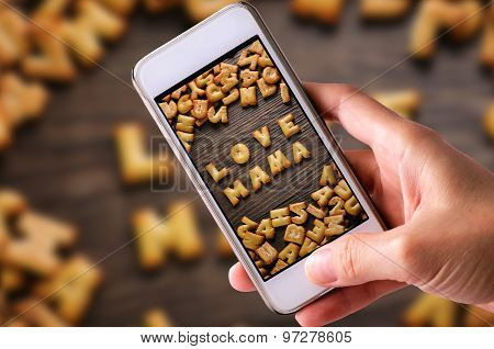 using mobile phones to take photos of Cookies ABC in the form of word LOVE MAMA alphabet on old wood