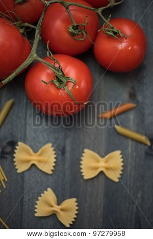 food background on rustic wood with pasta and tomatoes
