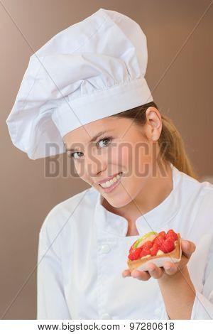 Baker holding strawberry tart