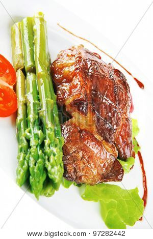 roasted beef meat served with asparagus on plate