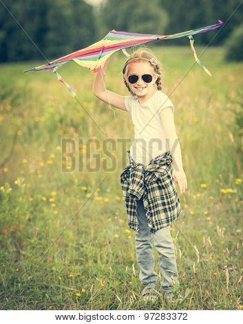 little cute girl posing with a kite in a meadow on a sunny day