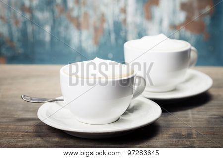Two cups of coffee on old wooden table