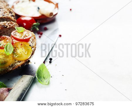 Delicious sandwich with slices of tomatoes and basil on white marble background
