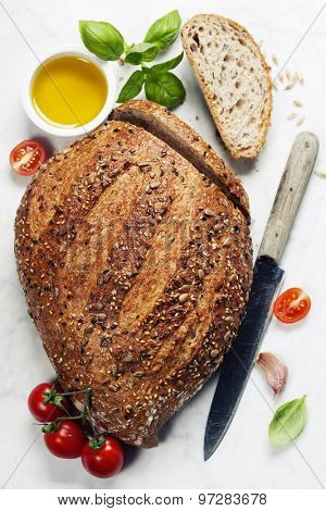 Large loaf of bread and ingredients for making sandwich on white marble background
