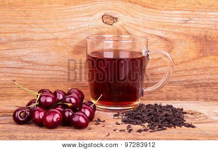 Cup Of Tea And Sweet Cherry On A Wooden Background