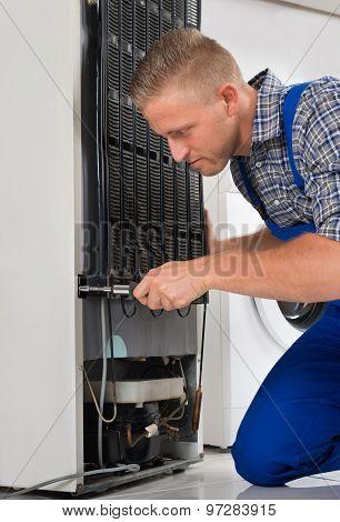 Worker Repairing Refrigerator In House