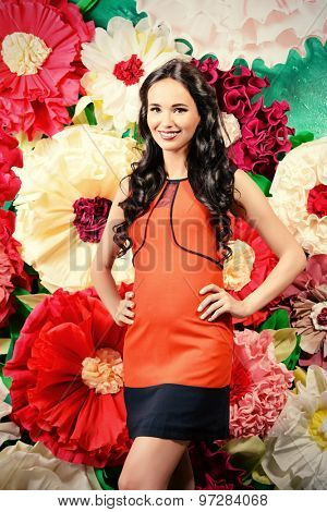 Portrait of a beautiful pregnant woman posing over big bright flowers. Clothes for pregnant women. Beauty, fashion.