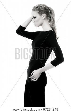 Black-and-white portrait of a beautiful slender female model in black fitting clothing posing over white background. Beauty, fashion. Body care. Isolated over white.