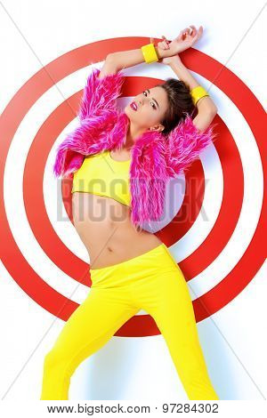 Fashion shot of a classy female model posing in vivid colourful clothes over red target. Bright fashion. Studio shot.