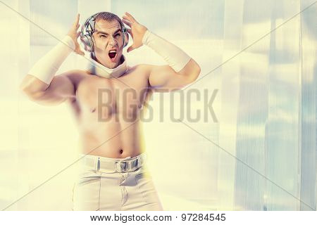 Expressive futuristic muscular man dancing and singing in headphones on a luminous transparent background. Music, technology. Futuristic DJ.