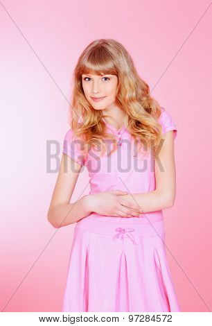 Pretty girl teenager posing in pink dress over pink background. Studio shot.