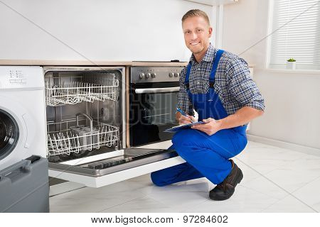 Handyman With Clipboard Looking At Dishwasher