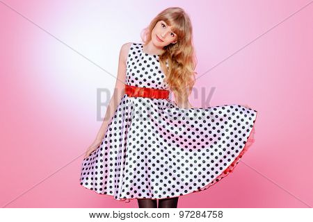 Portrait of a pretty teenager girl posing in pin-up dress over pink background. Beauty, fashion.