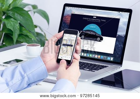 Man Orders Uber X Through His Iphone And Macbook With Uber Website On The Background