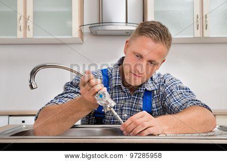 Plumber Fixing Faucet In Sink