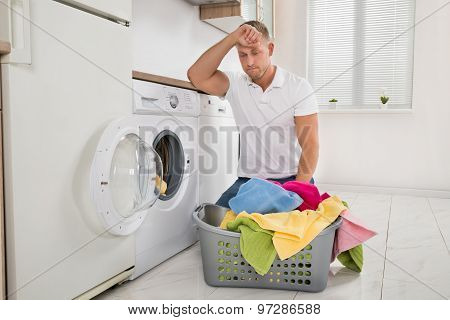 Tired Man Loading Clothes Into The Washing Machine