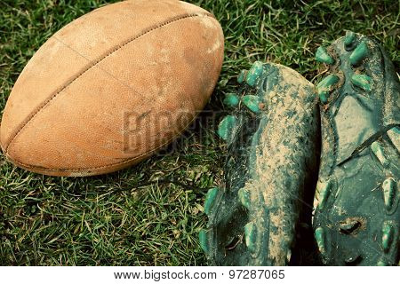 close up of an american football and sports shoes covered with mud
