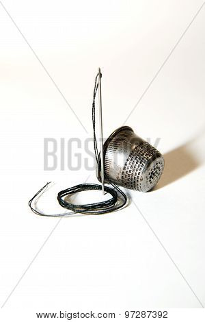 Iron Needle And Thimble On A White Background