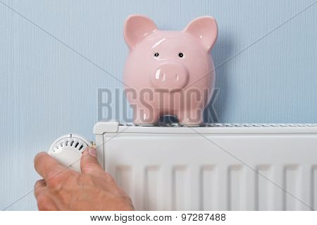Man Holding Thermostat With Piggy Bank On Radiator