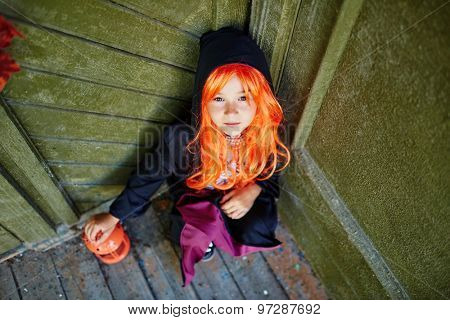 Youthful girl in Halloween attire looking at camera while sitting by wall of haunted house