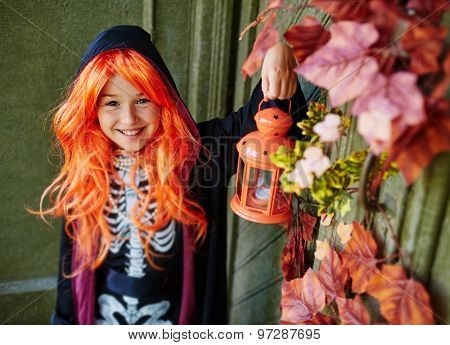 Cheerful girl in Halloween attire with lantern looking at camera