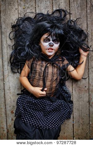 Furious little witch in wig and Halloween attire lying on wooden floor