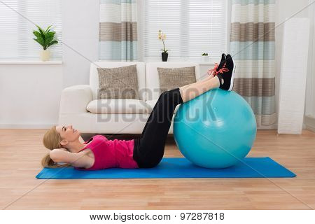 Woman Exercising With Fitness Ball In Living Room