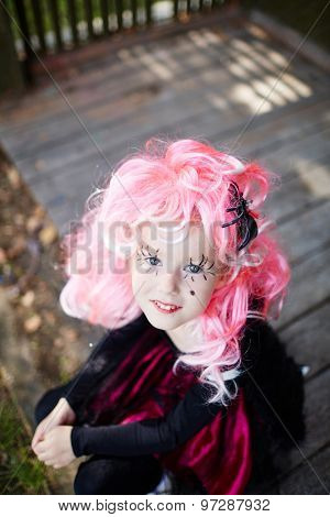 Halloween girl with spider in her pink hair looking at camera