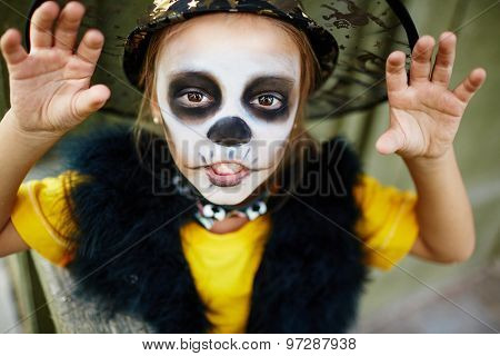 Halloween girl with painted face and frightening pose looking at camera