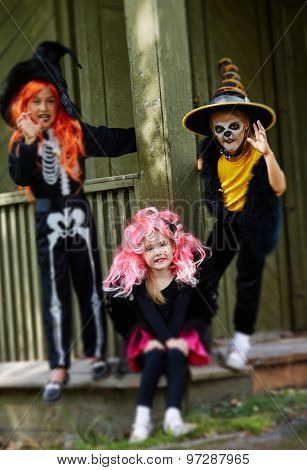 Group of friendly girls in Halloween attire standing by old house