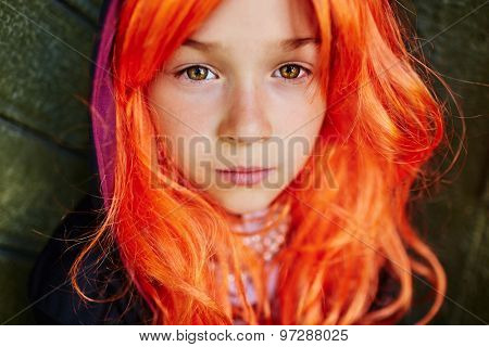 Calm girl with orange hair looking at camera