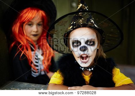 Little girl in Halloween attire looking at camera with frightening expression