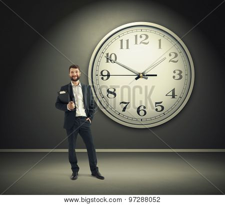 successful businessman holding black folder and looking at camera over big white clock on grey wall