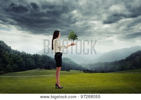 smiley woman holding young tree in her hands over beautiful landscape