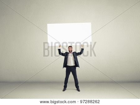 smiley businessman holding big white banner in grey empty room