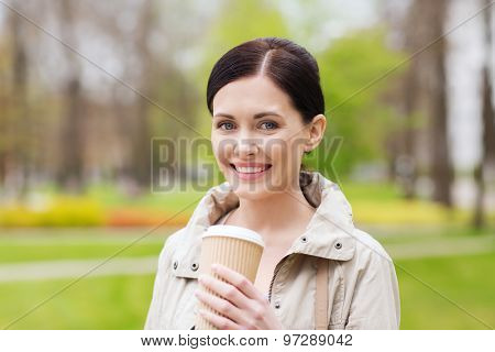 drinks, leisure and people concept - smiling woman drinking coffee in park