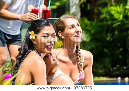 Two girls or women in vacation, Asian and Caucasian, in tropical garden at hotel pool tanning being served drinks or cocktails